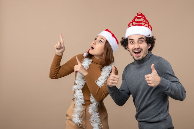 Umore natalizio con coppia adorabile soddisfatta fresca eccitata che indossa cappelli rossi di babbo natale divertendosi insieme