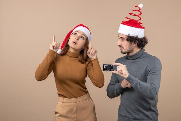 Umore di natale con la coppia cool soddisfatta eccitata che indossa il ragazzo rosso dei cappelli di babbo natale che mostra la carta di credito
