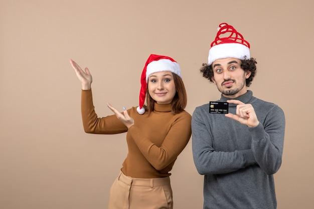 Umore natalizio con coppia cool emotiva soddisfatta eccitata che indossa cappelli rossi di babbo natale che mostra la carta di credito