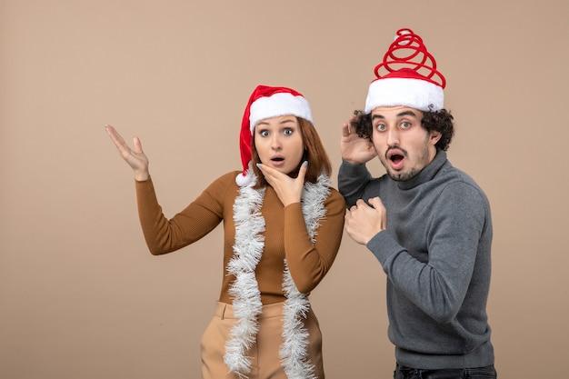 Umore di natale con le coppie fredde scioccate soddisfatte eccitate che portano i cappelli rossi del babbo natale che indicano sopra