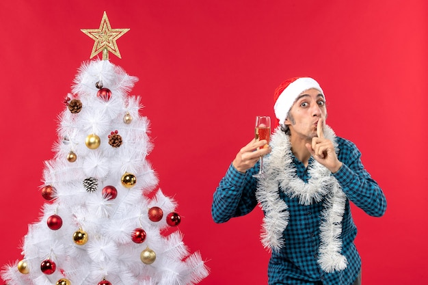 Xmas mood with happy crazy emotional young man with santa claus hat in a blue stripped shirt raising a glass of wine making silence gesture near christmas tree