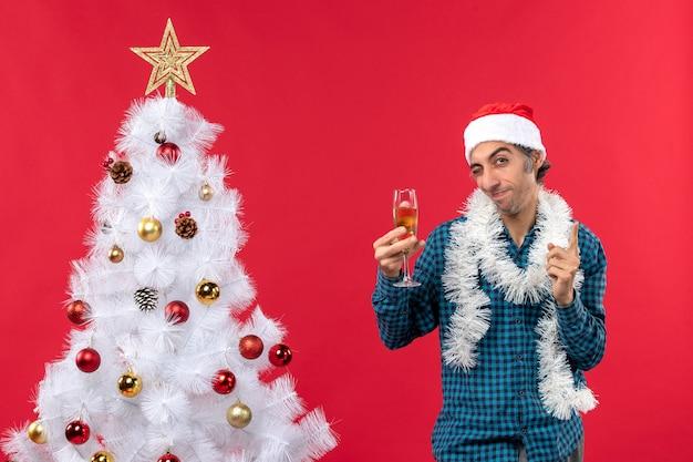 クリスマスツリーの近くでワインのグラスを上げる青い縞模様のシャツにサンタクロースの帽子をかぶった幸せな狂気の感情的な若い男とクリスマスムード