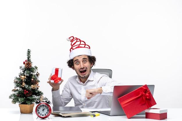 Рождественское настроение с нервным молодым бизнесменом в шляпе санта-клауса, держащим подарок и проверяющим свое время на белом фоне
