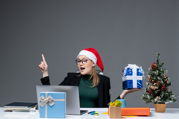 Atmosfera natalizia con giovane donna positiva con cappello di babbo natale e occhiali da vista seduti a un tavolo che mostra il regalo che punta sopra su sfondo scuro