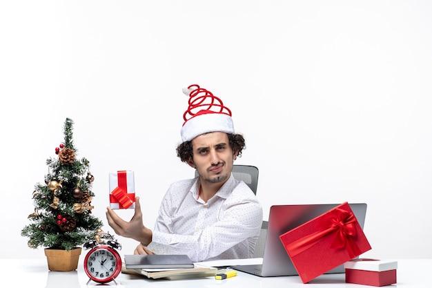 Atmosfera natalizia con orgoglioso giovane imprenditore con cappello di babbo natale e tenendo il suo dono di brainstorming su sfondo bianco