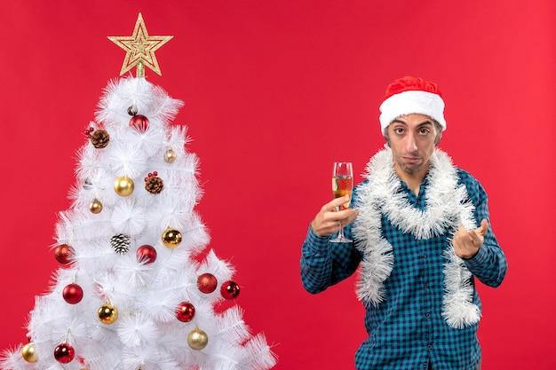Umore natalizio con giovane triste con cappello di babbo natale in una camicia blu spogliata che tiene un bicchiere di vino vicino all'albero di natale