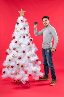 장식 된 크리스마스 트리 근처에 서서 자신감을 가지고 마이크와 전화 서를 들고 심각한 젊은 남자와 크리스마스 분위기