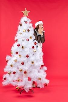 Atmosfera natalizia con scioccata giovane bella signora in un abito nero con cappello di babbo natale che si nasconde dietro il nuovo anno