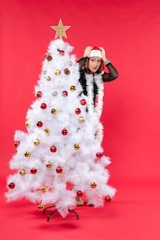 Atmosfera natalizia con scioccata giovane bella signora in un abito nero con cappello di babbo natale