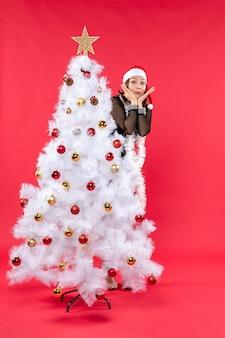 Рождественское настроение с потрясенной молодой красивой леди в черном платье с шапкой санта-клауса, прячущейся за новогодней елкой