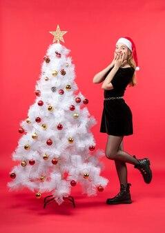 Umore di natale con giovane donna scioccata in abito nero e cappello di babbo natale in piedi vicino all'albero di natale bianco