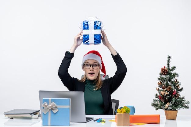 Atmosfera natalizia con giovane donna scioccata con cappello di babbo natale e occhiali da vista seduto a un tavolo che solleva regalo sulla sua testa sfondo bianco