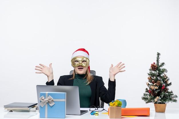 Atmosfera natalizia con giovane donna scioccata con cappello di babbo natale e maschera da portare seduto a un tavolo su uno sfondo bianco