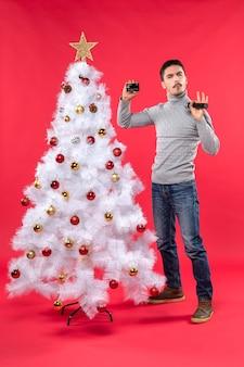 장식 된 크리스마스 트리 근처에 서서 마이크와 전화를 들고 뭔가에 대해 말하는 웃는 젊은 남자와 함께 크리스마스 분위기