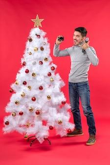 웃는 젊은 남자가 장식 된 크리스마스 트리 근처에 서서 마이크와 전화를 들고 전화를 걸어 제스쳐를 만드는 크리스마스 분위기