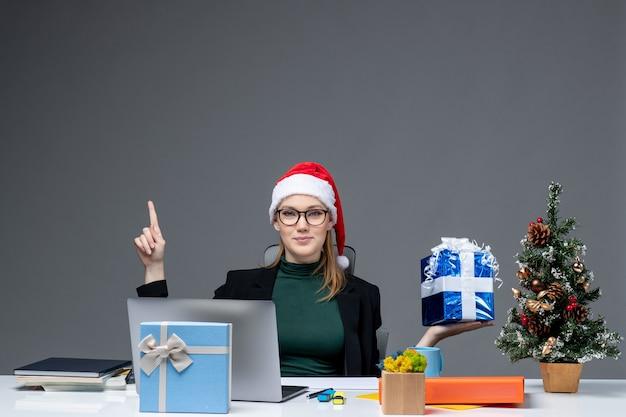 Atmosfera natalizia con sorridente giovane donna con cappello di babbo natale e occhiali da vista seduto a un tavolo che mostra il regalo che punta sopra su sfondo scuro