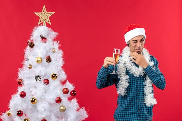 Umore natalizio con faccia acida giovane uomo con cappello di babbo natale in una camicia blu spogliata che tiene un bicchiere di vino vicino all'albero di natale