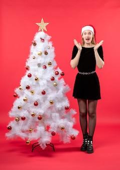 Umore natalizio con giovane donna sorpresa in abito nero e cappello di babbo natale in piedi vicino all'albero di natale bianco