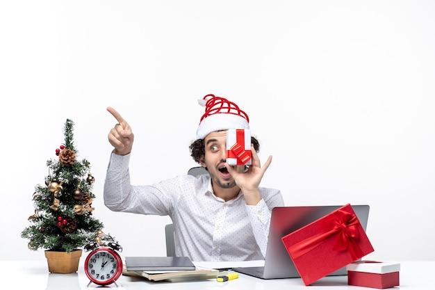 Рождественское настроение с удивленным деловым человеком в шляпе санта-клауса, поднимающим подарок к лицу и указывающим что-то на белом фоне