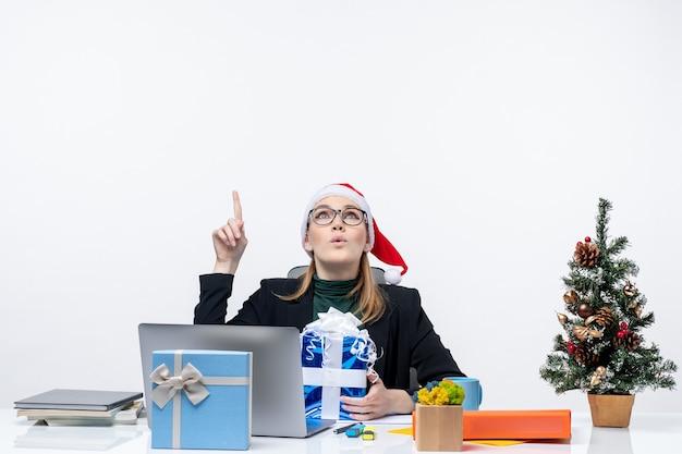 Atmosfera natalizia con giovane donna sorpresa con cappello di babbo natale e occhiali da vista seduto a un tavolo che tiene un regalo e che mostra sopra su priorità bassa bianca