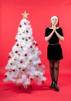 Umore natalizio con giovane donna premurosa in abito nero e cappello di babbo natale in piedi vicino all'albero di capodanno bianco