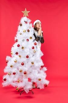 새 해 나무 뒤에 숨어있는 산타 클로스 모자와 검은 드레스에 아름 다운 아가씨와 크리스마스 분위기