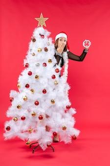 Рождественское настроение с молодой красивой леди с удивленным выражением лица в черном платье