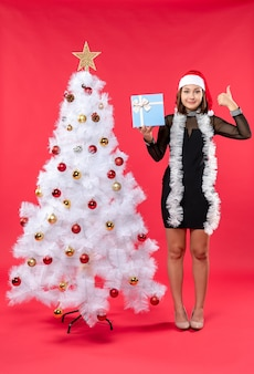 Xmas mood with young girl in a black dress with santa claus hat standing near christmas tree and holding new year gift showing above