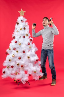 Xmas mood with young guy standing near decorated christmas tree and holding microphone and phone lookin above