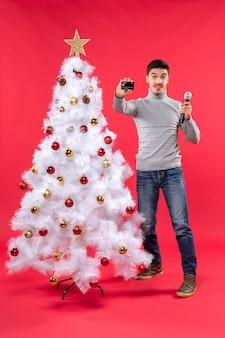 Umore di natale con il giovane ragazzo in piedi vicino all'albero di natale decorato e tenendo il microfono e mostrando il telefono
