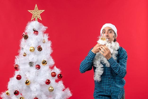 산타 클로스 모자와 와인 한 잔을 올리는 젊은 남자와 크리스마스 분위기가 크리스마스 트리 근처에서 자신을 환호합니다.