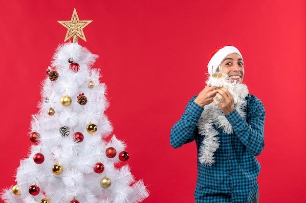 サンタクロースの帽子をかぶった若い男とクリスマスムードとワインのグラスを上げるクリスマスツリーの近くで彼自身を応援します