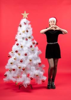 Umore natalizio con giovane donna in abito nero e cappello di babbo natale in piedi vicino all'albero di natale bianco e facendo un gesto del cuore