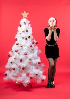 Umore natalizio con giovane donna in abito nero e cappello di babbo natale in piedi vicino all'albero di natale bianco e l'invio di gesto di bacio