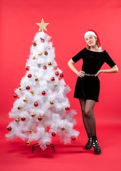 Рождественское настроение с молодой женщиной в черном платье и шляпе санта-клауса, стоящей возле белой новогодней елки, stock photo
