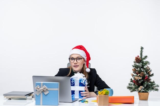 サンタクロースの帽子をかぶって、白い背景の上に贈り物とその上に新年のツリーを飾ったテーブルに座って眼鏡をかけている若い女性とクリスマス気分