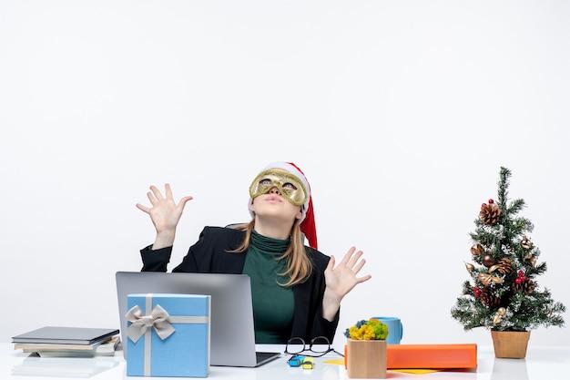 サンタクロースの帽子と白い背景の上に上を見ているテーブルに座ってマスクを身に着けている若い女性とクリスマス気分