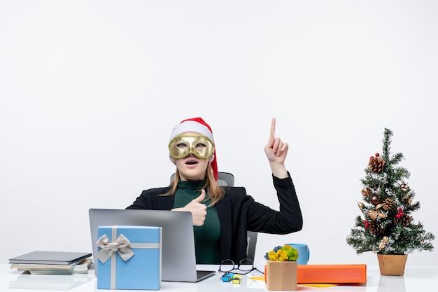 サンタクロースの帽子をかぶって、白い背景の上で大丈夫なジェスチャーをする上を指すテーブルに座っているマスクを身に着けている若い女性とクリスマス気分
