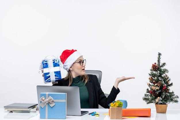 Atmosfera natalizia con giovane donna con cappello di babbo natale e occhiali da vista seduto a un tavolo che tiene il suo regalo facendo domande su sfondo bianco