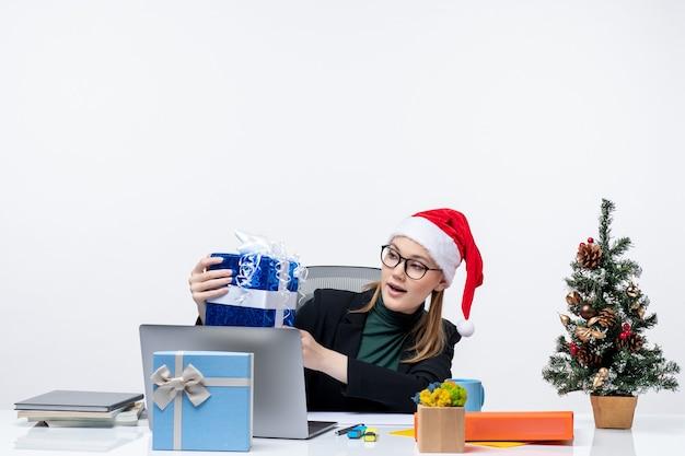 Atmosfera natalizia con giovane donna con cappello di babbo natale e occhiali da vista seduto a un tavolo tenendo il suo regalo su sfondo bianco
