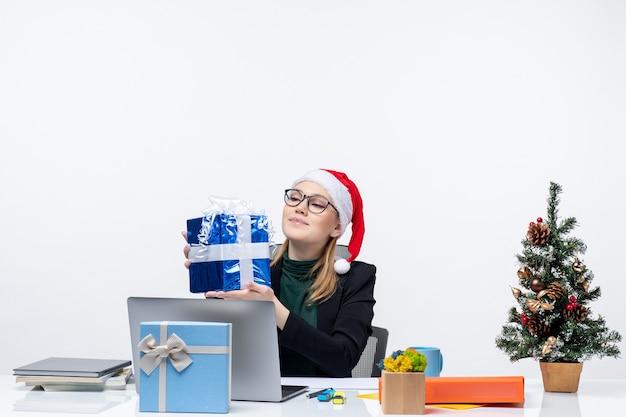Atmosfera natalizia con giovane donna con cappello di babbo natale e occhiali da vista seduto a un tavolo guardando il suo regalo con orgoglio su sfondo bianco