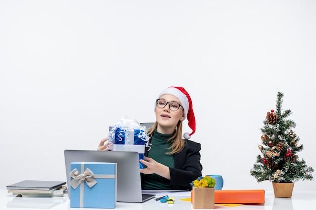 Atmosfera natalizia con giovane donna con cappello di babbo natale e occhiali da vista seduto a un tavolo che riceve un regalo su priorità bassa bianca