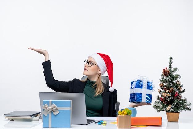 Atmosfera natalizia con giovane donna con cappello di babbo natale e occhiali da vista seduto a un tavolo che mostra il regalo che punta qualcosa su sfondo bianco