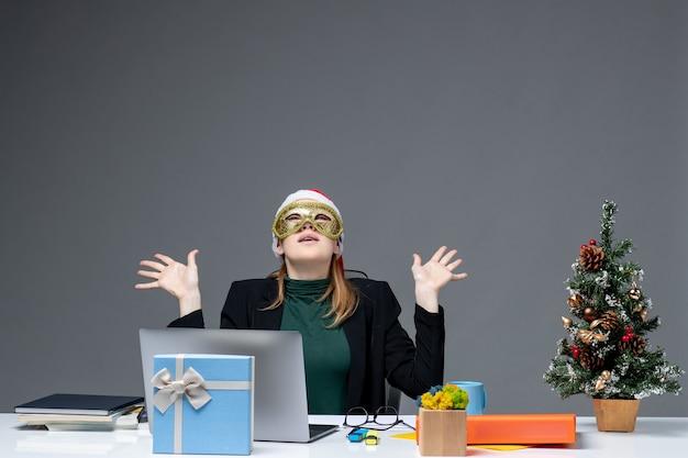Atmosfera natalizia con giovane donna con cappello di babbo natale e maschera da portare seduto a un tavolo guardando sopra su sfondo scuro