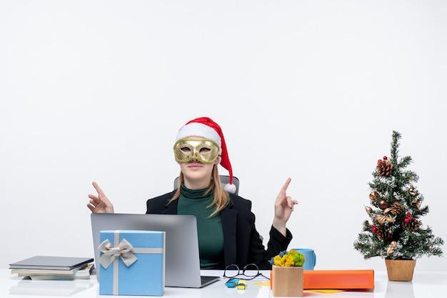 Atmosfera natalizia con giovane donna con cappello di babbo natale e maschera da portare seduto a un tavolo che punta qualcosa su sfondo bianco