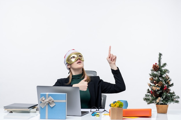 Atmosfera natalizia con giovane donna con cappello di babbo natale e maschera da portare seduto a un tavolo che punta sopra su sfondo bianco