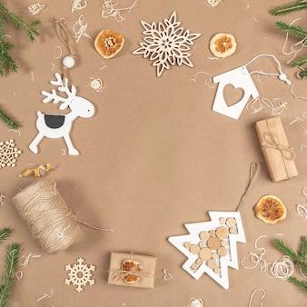 크리스마스 또는 새해 구성. 프레임, 테두리는 상자, 꼬기, 나무 장식, 말린 오렌지, 가문비나무 가지로 만든 베이지색 배경입니다. 개념 제로 폐기물 메리 크리스마스 복사 공간입니다.