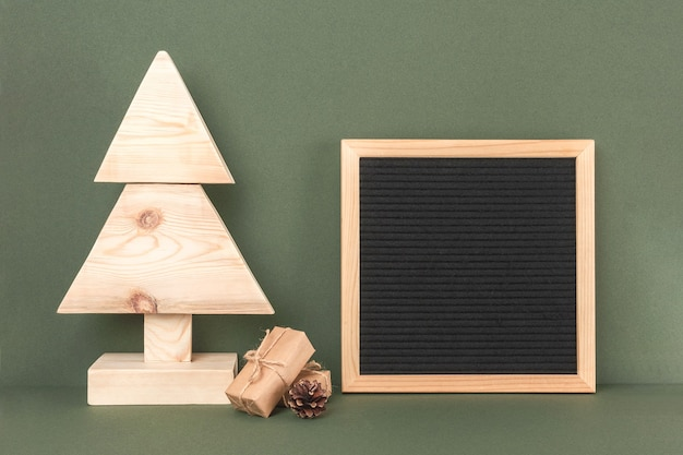 Рождество или новогодний состав. самодельная деревянная елка, подарки и пустая доска для писем на зеленом фоне