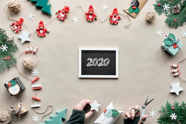 Креативный декор ручной работы, безотходная новогодняя рамка на новый год. плоская планировка, вид сверху на крафт-бумагу. текстильные безделушки, подарок в руки. эко дружественных xmas party концепция. мелом рисунок 2020 на доске.