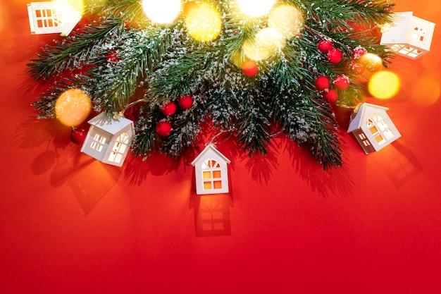 Рождественский красный фон с заснеженными еловыми ветками, светящимися рождественскими огнями, белыми домиками с красивыми тенями и золотыми огнями боке. уютное рождество дома концепции. вид сверху. скопируйте пространство.